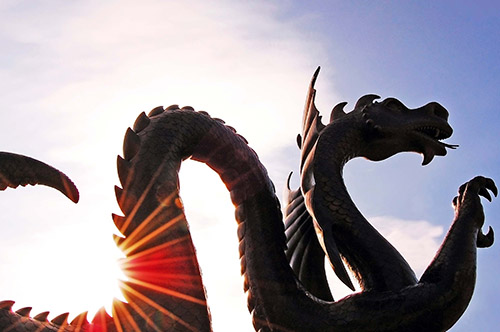 Dragon mascot statue backlit against sky